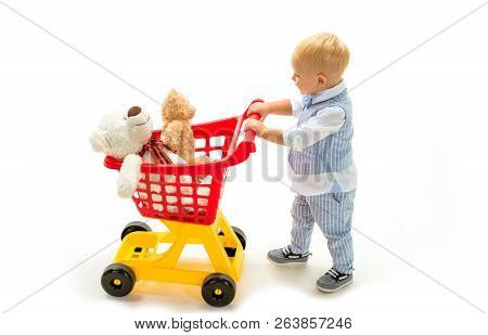Happy Childhood And Care. Little Boy Go Shopping With Full Cart. Savings On Purchases. Shopping For