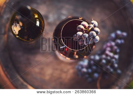A Glass Of Wine And A Bottle Of Red Wine On A Wooden Barrel