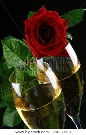 a two glasses of champagne with the ring inside