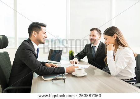 Smiling Accountant Discussing Plan With Colleagues In Office