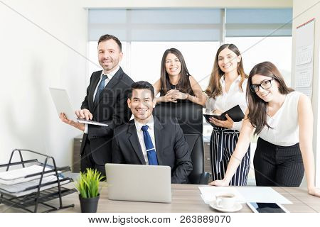 Group Of Successful Accountants Looking At Camera And Smiling In Office