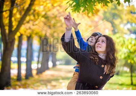Cute, Happy, Boy Smiling And Hugging With His Mom Among Yellow Leaves. Little Child Having Fun With