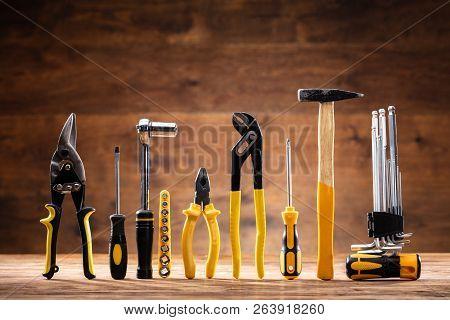 Row Of Various Worktools On Wooden Desk