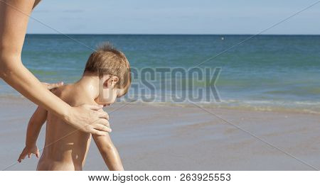 Mother Applying Sunblock Cream To Her Little Son On Back. Idyllic Beach Background
