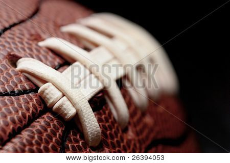 american football - macro over black with shallow depth of field and focus on first seam