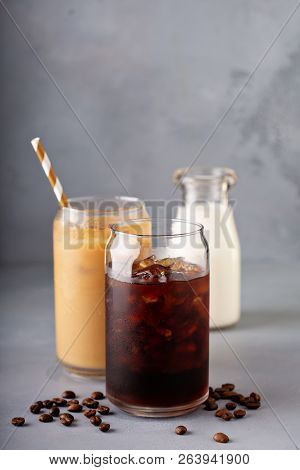 Cold Brew Iced Coffee In A Glass With Milk Or Creamer On Gray Background With Copy Space