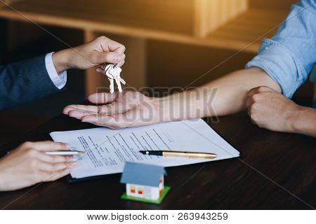 Real-estate Agent Giving Keys To New Property Owners After Signing Contract.concept Agreement And Re