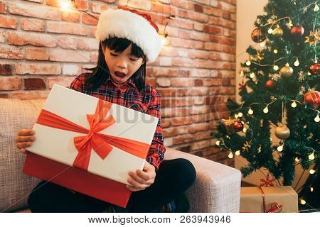 Christmas Girl Kid In A Santa Hat Opening Mouth. Cute Child Open Gift Box With Red Ribbon At Home. D