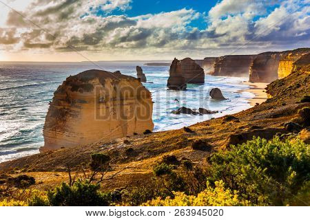The concept of exotic, active and photo-tourism. Rocks of the Twelve Apostles at sunset. Grandiose coast of Australia