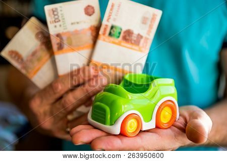 Hand Hold Green Toy Car And Russian Money.fixed Rate For Car Loan, Or Saving Money For Car, Trade Ca