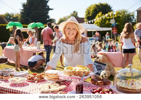 Portrait Of Mature Woman Serving On Cake Stall At Busy Summer Garden Fete