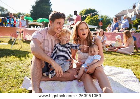 Family With Children Sitting On Rug At Summer Garden Fete
