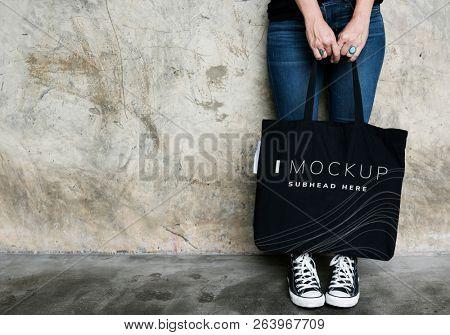 Woman carrying a black tote bag mockup