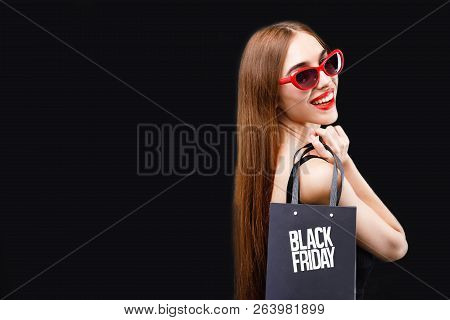 Elegant Rich Brunette Woman Wearing Black Dress And Sunglasses Posing With Black Friday Shopping Bag
