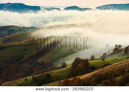 Fog And Rising Clouds Roll Over The Rural Hills. Gorgeous Autumn Scenery In Mountains At Dawn