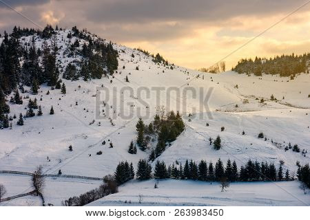 Lovely Sunset In Mountains. Yellow Glowing Sky Above The Snow Covered Hill