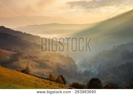Amazing Glowing Sunrise In Mountains. Countryside In Fall Colors. Village Down In The Valley In Haze
