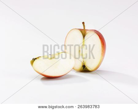 An Apple Sliced In Half With A Portion In Front On A White Background