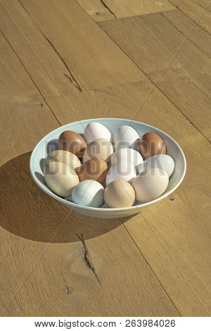 A Bowl Of Various Coloured Eggs On A Wooden Surface