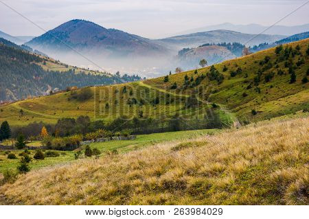 Lovely Autumn Scenery Of Mountainous Countryside. Dull Overcast Sky Above The Rolling Hills Of Rural