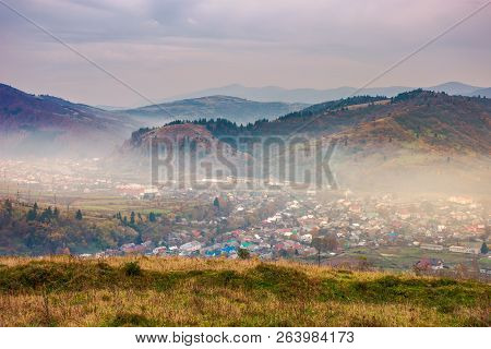 Autumn Countryside In Mountains. Small Town In Hazy Valley. Forested Hills In Fall Colors. Gloomy Af