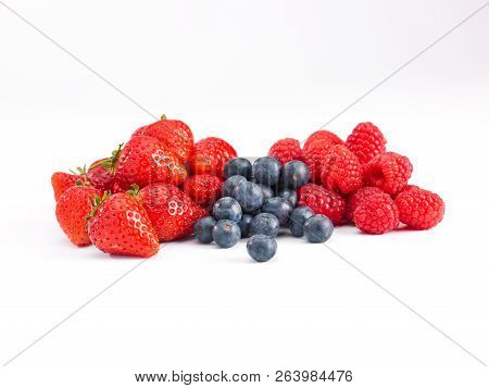 A Selection Of Strawberries, Rasperries And Blueberries On A White Background