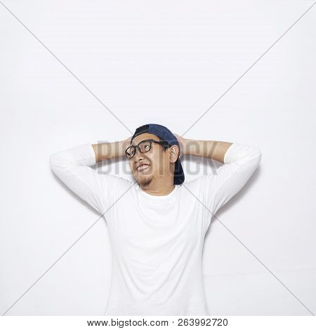 Photo Image Of Young Asian Man Looked Happy, Thinking And Looking Up, Hands Behind Head, Having Good