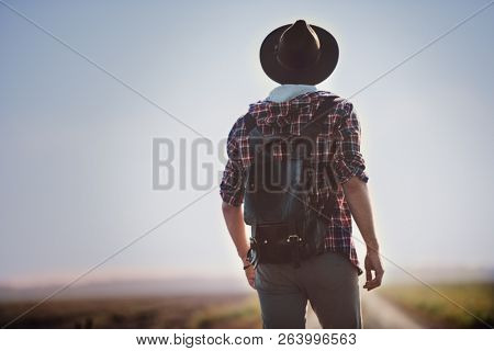 A shot of a man walking far away on the road in the countryside. Fashion for men. Comfortable, casual clothes.