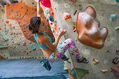 Strength and endurance training. The climber trains on the climbing wall. A woman trains to climb on an artificial relief. A slender girl goes in for sports. poster
