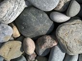 rough colored stones in on a sunlit beach. - - color space: adobe rgb (1998) poster