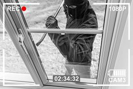 CCTV view of burglar breaking in to home through window with crowbar