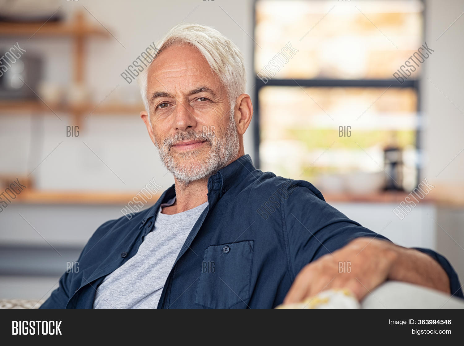 Handsome senior man with white hair sitting on couch and looking at camera. Satisfied old man relaxing on sofa while looking at camera. Portrait of proud mature man stay at home with copy space.