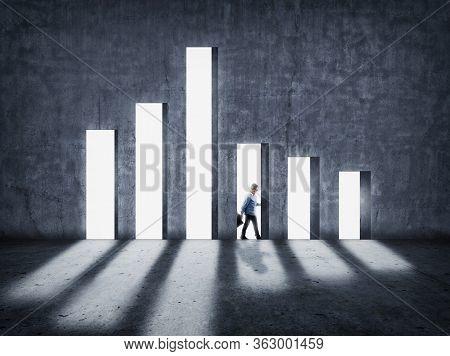 Decreasing Chart On Concrete Wall . Businessman Walking Behind Graph . Economy Crisis Concept .