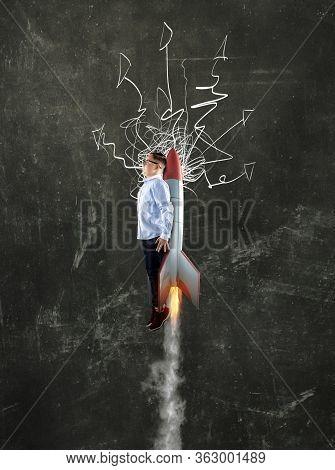 Businessman Flying With Rocket Missle In Front Of Blackboard. Blackboard Drawn With Arrows .