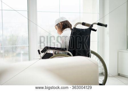 Little boy sitting in wheelchair looking trough window