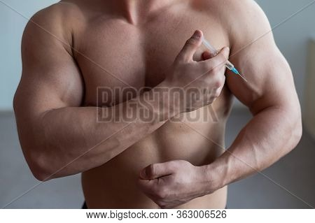 A Muscular Man With A Naked Torso Holds A Dope Syringe. Unrecognizable Bodybuilder Puts Himself Ster