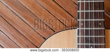 Acoustic Guitar On A Wooden Background With Copy Space.the Guitar Is A Fretted Musical Instrument Th