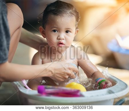 Mother Bathes The Kid Concept. Adorable Girl In Bathtub With Fluffy Soap Bubble. Mom Bathing Infant.