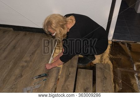 Laying Laminate Or Parquet In The Room, Worker Laying Wood Or Linoleum Laminate On The Floor And Mar