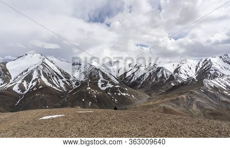 Ak-baital Pass, Tajikistan - June 26, 2019: Man On A Mountain At The Ak-baital Pass With View On Sno