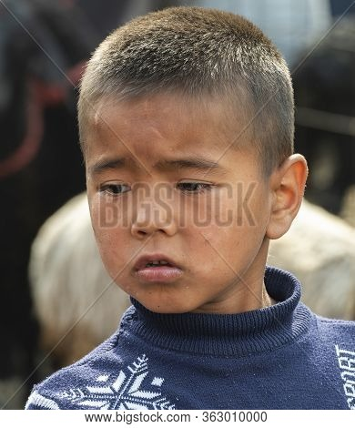 Osh, Kyrgyzstan - June 30, 2019: Boy On The Livestock Market Between Sheep And Goats In Osh, Kyrgyzs