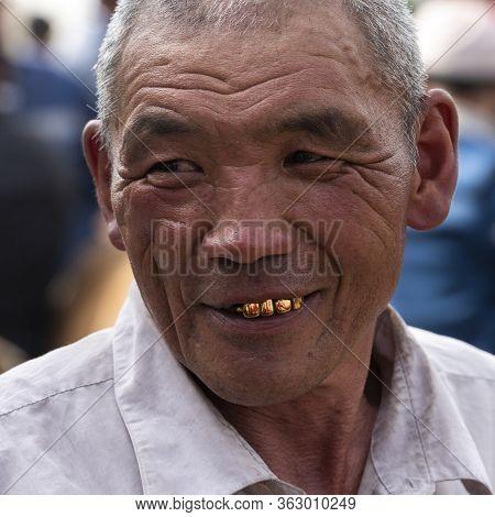 Osh, Kyrgyzstan - June 30, 2019: Man With Golden Teeth On The Livestock Market In Osh, Kyrgyzstan.