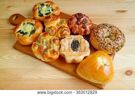 Delectable Assorted Sweet And Savory Breads On A Wooden Tray Served On Wooden Table