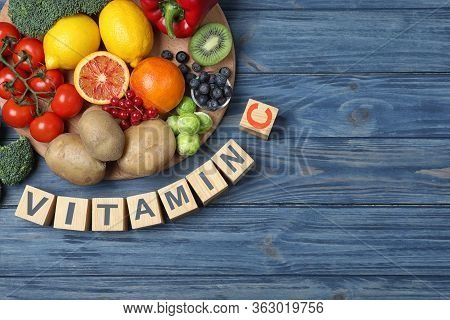 Cubes With Phrase Vitamin C And Fresh Products On Blue Wooden Table, Flat Lay. Space For Text