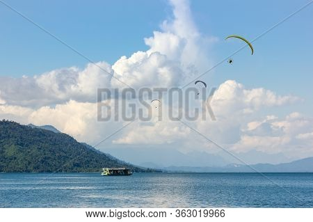 Parachute Flying Over Ridge Of Dam With Background Mountains  In Laos. At Nam Ngum Dam Laos