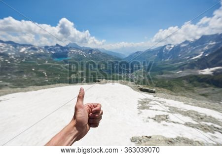 Close Up Of Man Hand Doing Approval Gesture With Grassy Hills And Beautiful Sky On Background. Mount