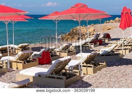 Sun Loungers With Umbrellas On Ellie Beach In Rhodes Town. Greece