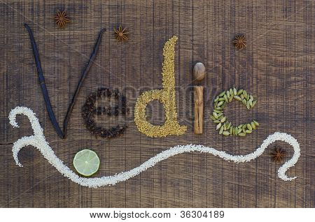 The word Vedic spelled out in a decorative way with spices and seeds used in the ayurveda diet and healing on a wooden countertop surface. poster