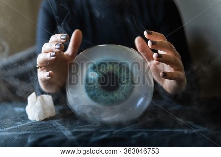 Fortune Teller Holding Hands Above Magic Crystal Ball With An Eye Iris Inside