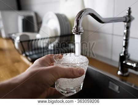 Man Filling A Glass Of Water From A Stainless Steel Kitchen Tap. Male's Hand Pouring Water Into The